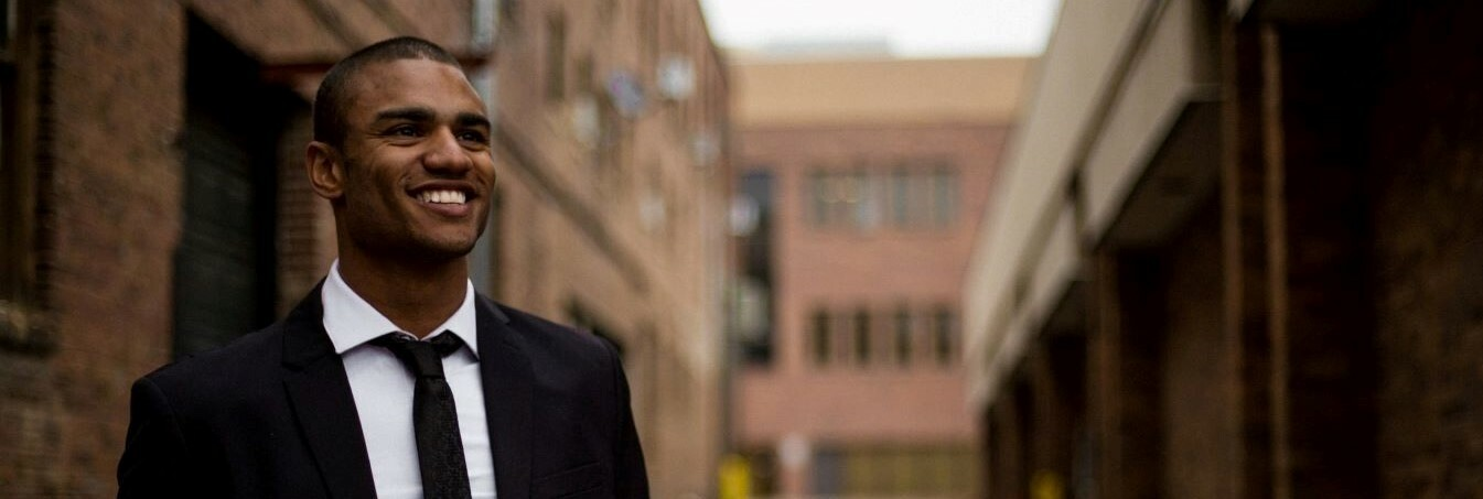 Man in a suit smiling with a street with large brick buildings in the background