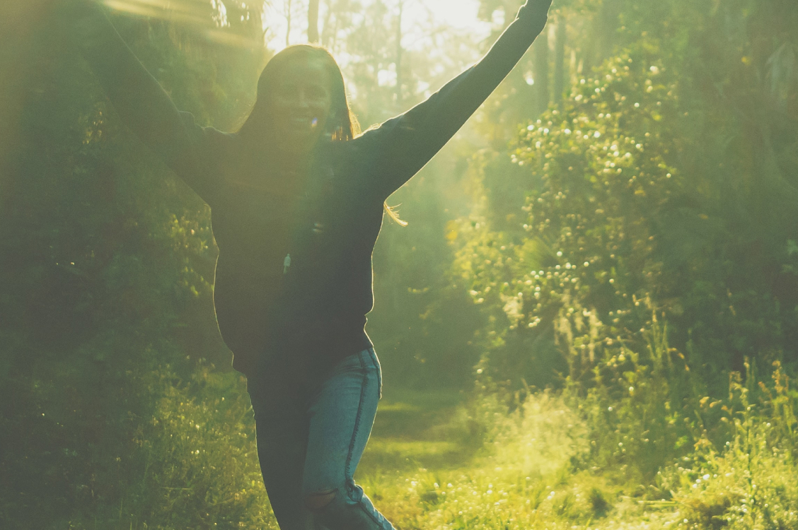 Girl running through a forest with her hands in the air